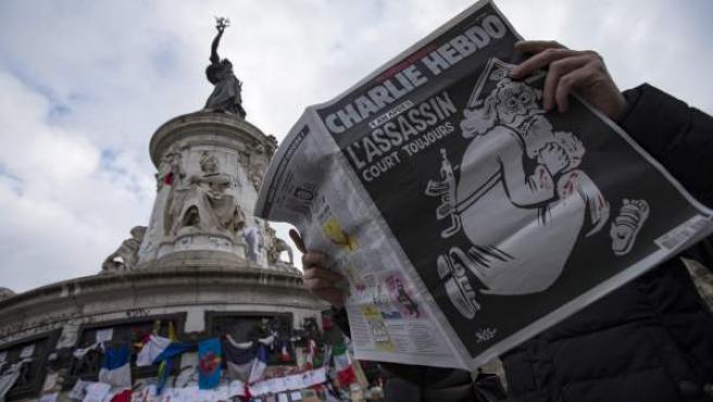 Un hombre ojea el número especial publicado por el semanario satírico Charlie Hebdo con motivo del primer aniversario del atentado yihadista contra su redacción, en la Plaza de la República de París (Francia).
