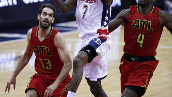 El jugador de Wizards Brandon Jennings (c) conduce el balón ante la marca de José Calderón (i) y Paul Millsap (d), de los Hawks.