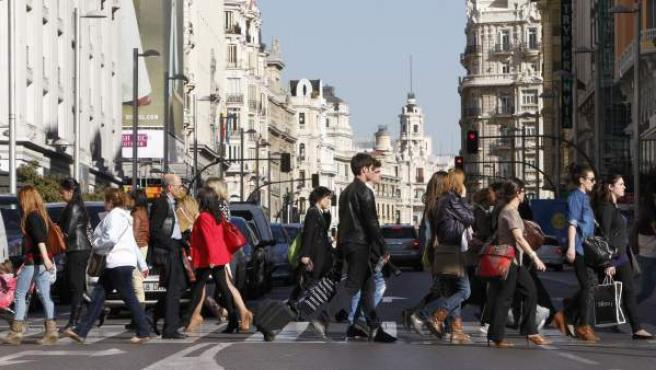 Un grupo de personas cruza por un paso de peatones en la céntrica Gran Vía de Madrid.