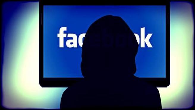 La silueta de una mujer frente a un monitor con el nombre de Facebook.
