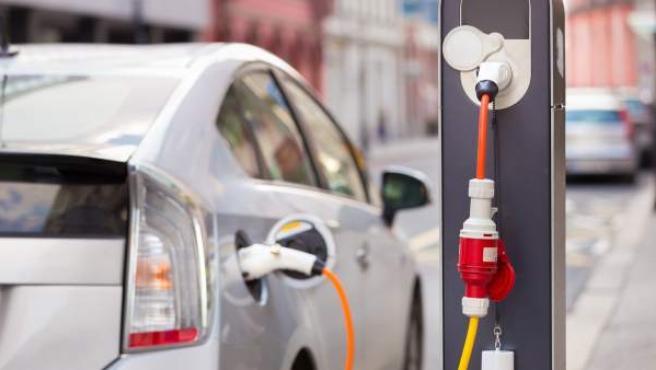 Un coche eléctrico, estacionado y enchufado en un punto de recarga.