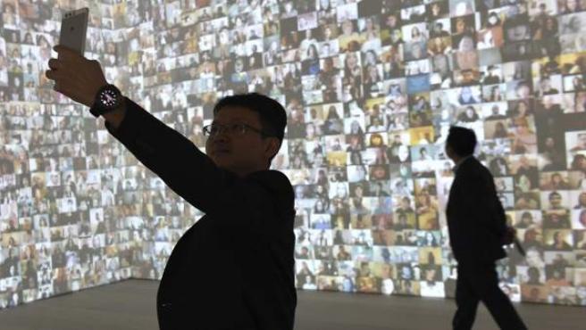 Un visitante se hace un selfi durante la inauguración de la exposición 'Selfie to Self-Expression' en la Saatchi Gallery de Londres.