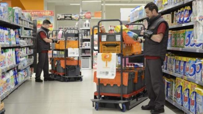 Dos trabajadores realizan un pedido online en un supermercado de Alicante.