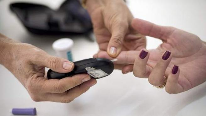 Un sanitario efectuando un control de glucemia en sangre.