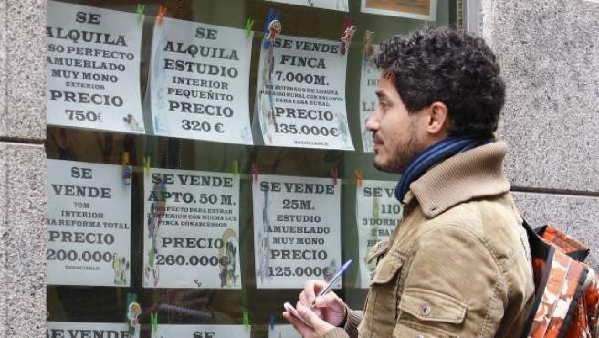 Un joven observa el escaparate de una inmobiliaria en Madrid.