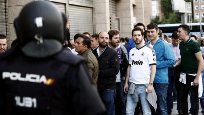 Agentes de la Policía y aficionados, en las inmediaciones del Vicente Calderón.