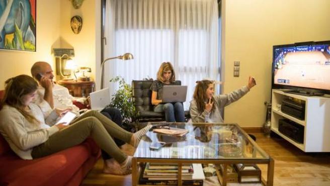 Una familia sentada frente al televisor.