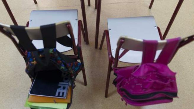 Sillas con mochilas en un colegio.