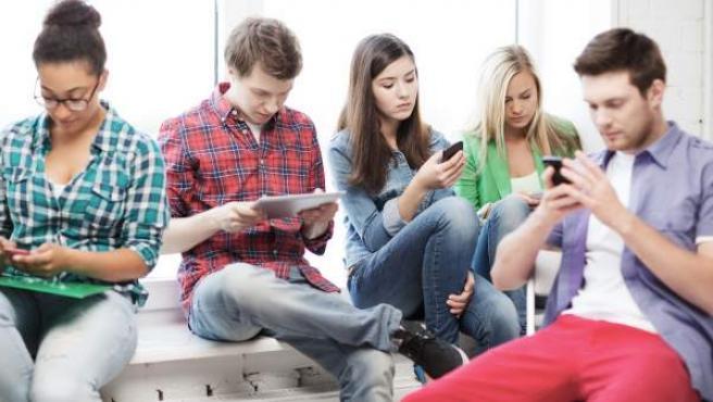 Un grupo de adolescentes consulta sus dispositivos móviles.