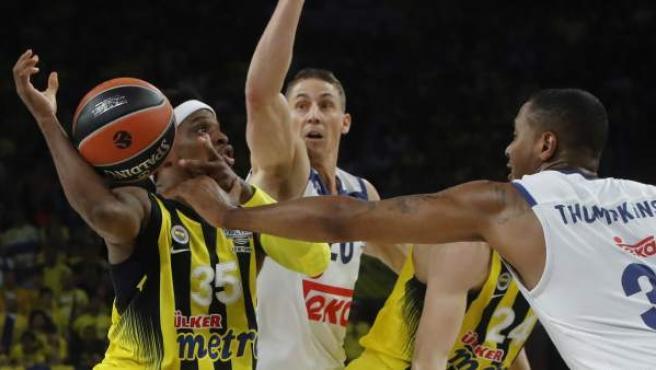 El base de Fenerbahçe Bobby Dixon (i) lucha un balón con los estadounidenses Jaycee Carroll (c) y Trey Thompkins (d), del Real Madrid, durante la segunda semifinal de la Final a Cuatro de la Euroliga