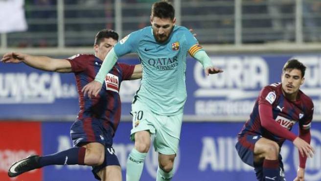 El delantero argentino del FC Barcelona Leo Messi (c) disputa un balón con el defensa Ander Capa (i), del Eibar, durante el partido de la decimonovena jornada de Liga en Primera División.