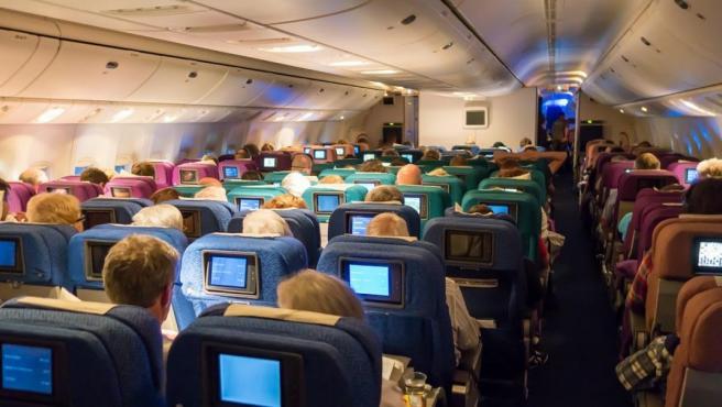 Pasajeros, en el interior de un avión en pleno vuelo.