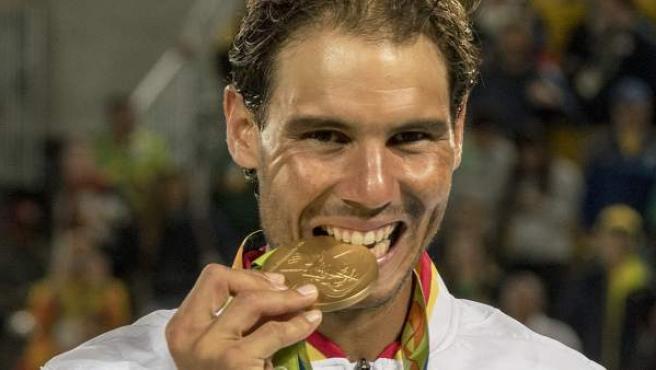 Rafa Nadal muerde su medalla de oro conseguida en el torneo de dobles masculinos en los Juegos de Río 2016.