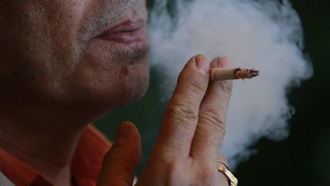 Un hombre fuma un cigarro.
