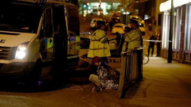 Una mujer, junto con un grupo de policías en una calle cerca del Manchester Arena, en Manchester, Reino Unido, donde se produjo una explosión al terminar un concierto de Ariana Grande, con el resultado de al menos 22 muertos.