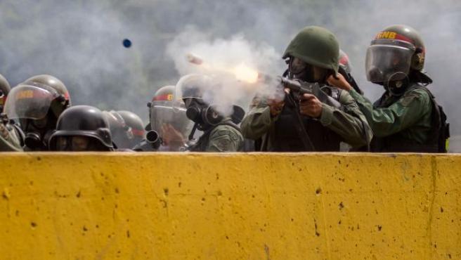 Agentes de la Guardia Nacional Bolivariana disparan bombas de humo para dispersar a unos manifestantes, en Caracas (Venezuela).