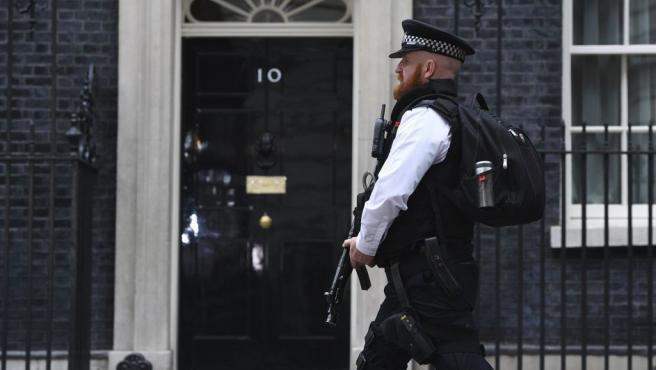Un policía armado vigila la calle donde se encuentra el Nº 10 de Downing Street.