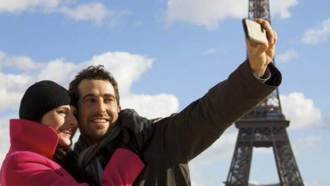 Una pareja se hace fotos con el móvil en París.