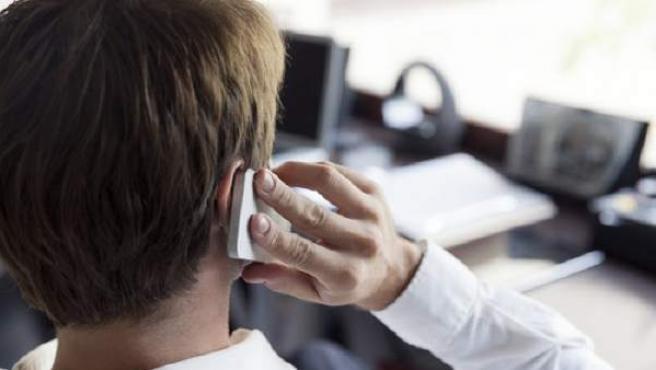 Una hombre habla por el móvil en su oficina.