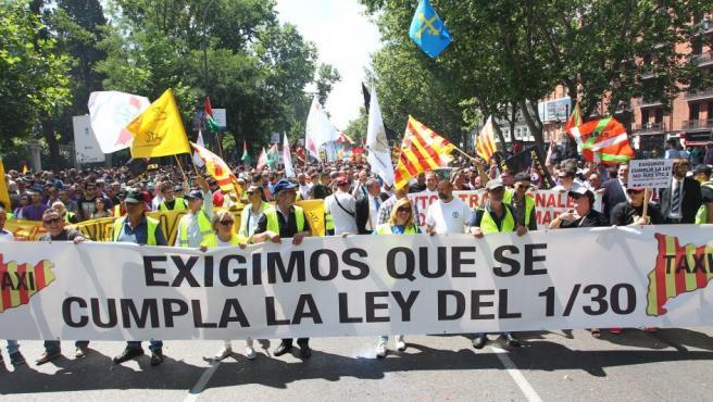 Imagen que muestra la pancarta que encabeza la marcha de taxistas en Madrid, camino del Congreso de los Diputados.