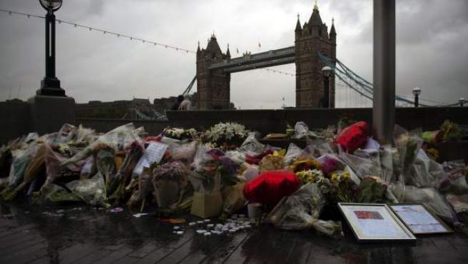 Varios ramos de flores, velas y mensajes dejados en memoria de las víctimas en los alrededores del Ayuntamiento, en Londres (Reino Unido).