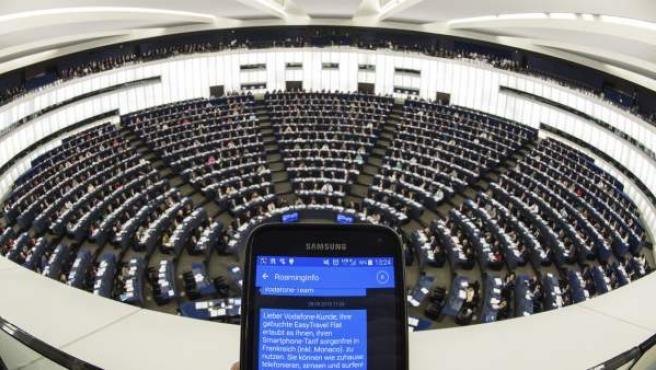 Una persona muestra un SMS con información de roaming en su teléfono móvil durante el pleno del Parlamento Europeo en Estrasburgo (Francia).