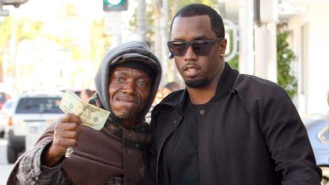 El cantante Sean 'P. Diddy' Combs le da un billete de 20 dólares a un 'sin techo' con el que a continuación se hace una foto en Beverly Hills (EE UU), el 2 de noviembre de 2011.