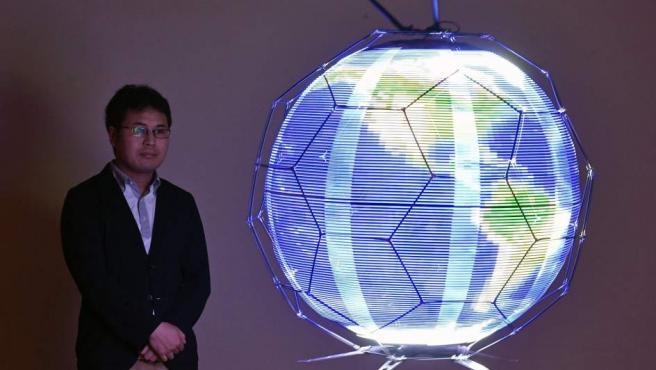 Un empleado de NTT DOCOMO observa un dron esférico que proyecta imágenes LED, durante una demostración en Yokosuka (Japón).