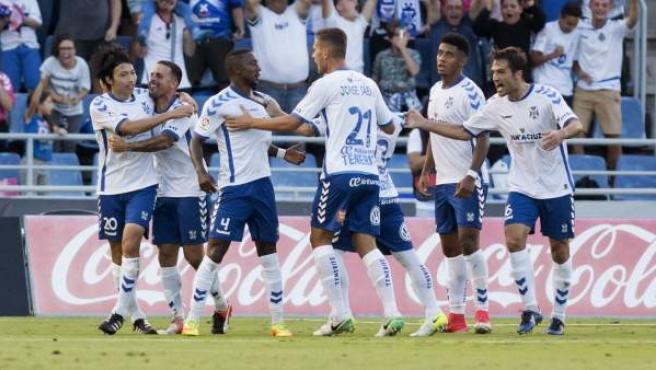 El delantero japonés del CD Tenerife, Gaku Shibasaki (i), recibe la felicitación de sus compañeros tras conseguir el primer gol ante el Cádiz en el partido de vuelta de la primera eliminatoria por el ascenso a LaLiga Santander.