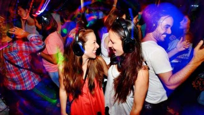 En la imagen varios jóvenes bailan en una discoteca.