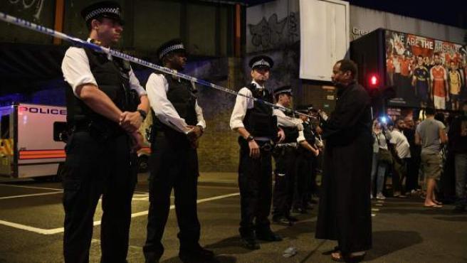 Varias personas junto al cordón policial en la zona donde una furgoneta atropelló a varios fieles que salían de la mezquita.