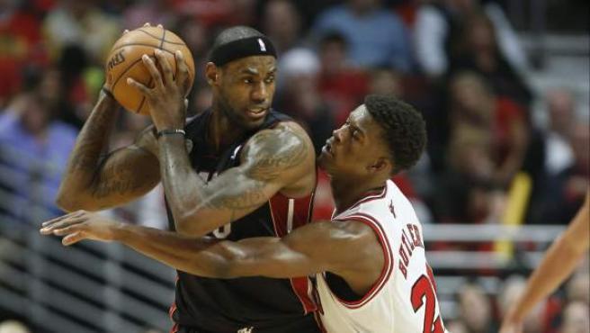LeBron James, de Miami Heat, protege el balón ante Jimmy Butler, de Chicago Bulls.