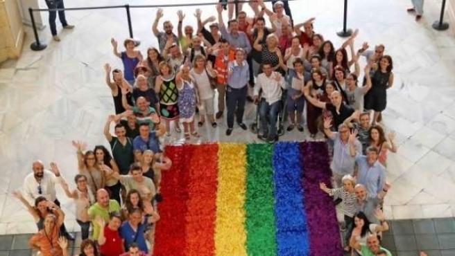 La corporación municipal del Ayuntamiento de Madrid junto a una bandera del World Pride.