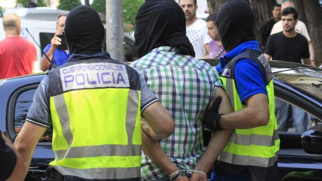 Agentes de la Policía Nacional trasladan a un presunto yihadista marroquí detenido en Madrid.