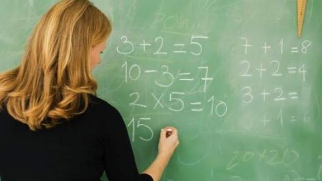Una profesora enseña matemáticas en un colegio.