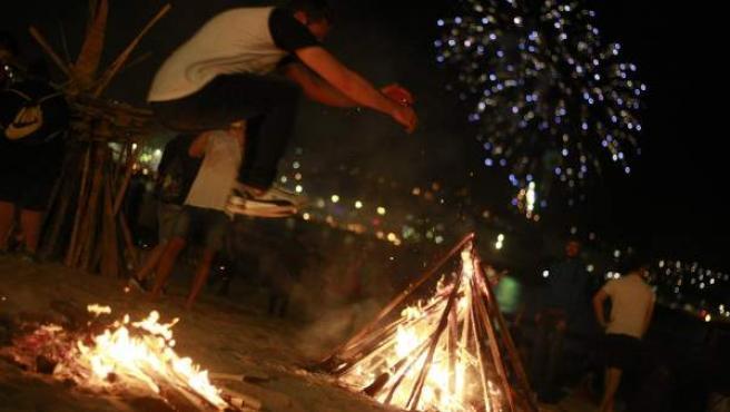 <p>Un hombre salta una hoguera de San Juan en Galicia.</p>