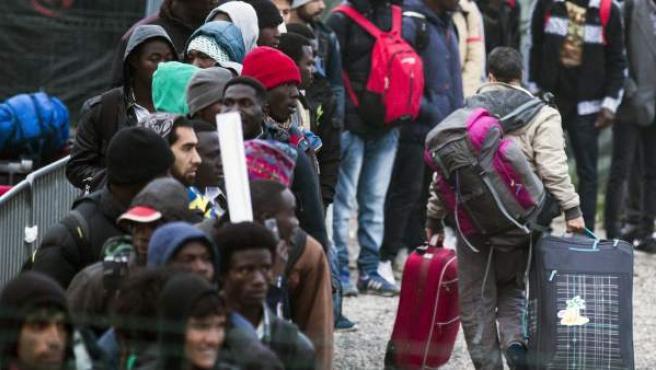 Varios migrantes esperan una cola en el centro de recepción de corta estancia en el campamento conocido como 'La Jungla' durante su desmantelamiento en Calais (Francia).