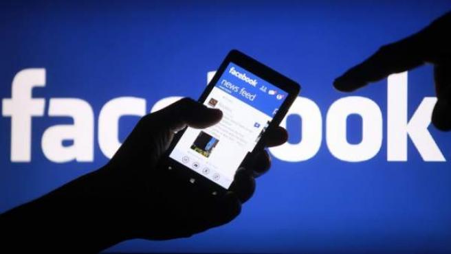 Un usuario consulta la red social Facebook desde su smartphone.