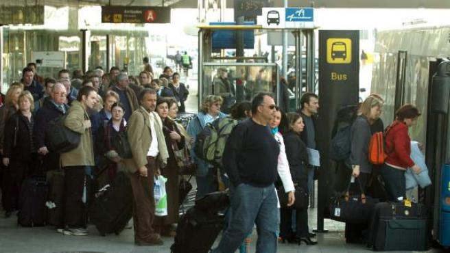Turistas y viajeros esperando el autobús que conecta el Aeropuerto de Barcelona-El Prat con la ciudad, en una imagen de archivo.