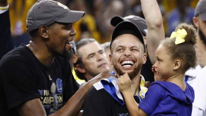 El jugador de Golden State Warriors Kevin Durant (i) celebra junto a su compañero de equipo Stephen Curry (c), tras ganar ante Cleveland Cavaliers en el partido cinco del juego de baloncesto de la NBA en el Oracle Arena de Oakland, California, Estados Unidos.
