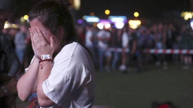 Una chica se lamenta del accidente sufrido por un acróbata que participaba en un espectáculo de entretenimiento en el intermedio de los conciertos de Alt-J y Green Day, dentro del programa del festival Mad Cool en Madrid.