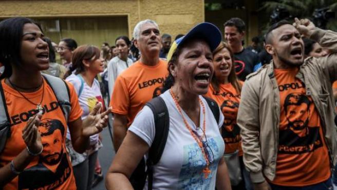 Militantes del partido Voluntad Popular gritan consignas en la entrada de la casa del opositor venezolano Leopoldo López, en Caracas.