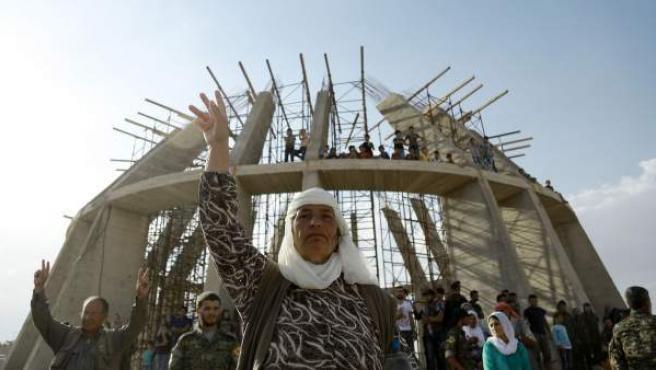 Una mujer y varios solados hacen el símbolo de la victoria en Kobane, ciudad kurda que se convirtió en el primer símbolo de la lucha contra Estado Islámico.