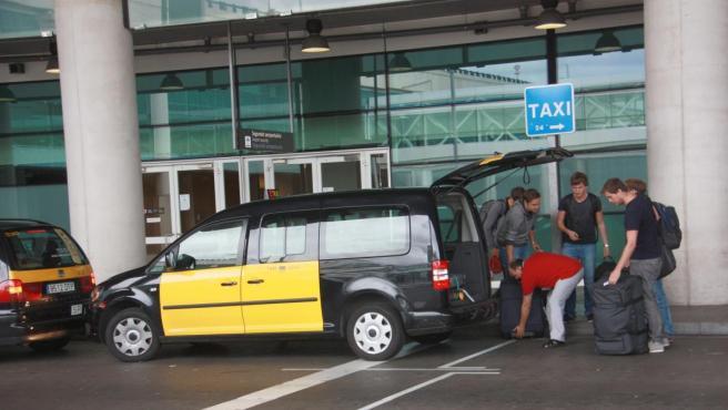 Un taxi de Barcelona recoge a unos turistas en el aeropuerto del Prat.