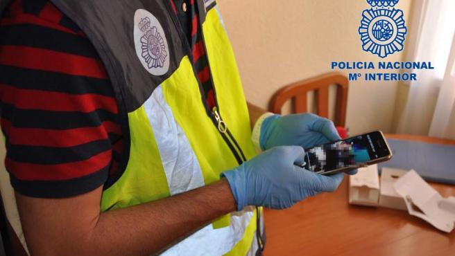 Un agente del Cuerpo Nacional de Policía revisa el contenido del teléfono móvil.