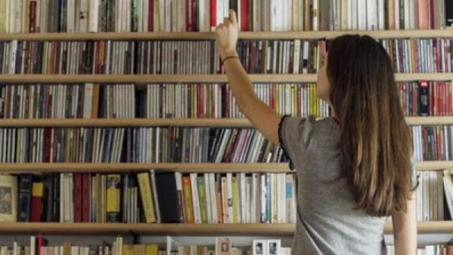 Una mujer cogiendo un libro de una estantería.