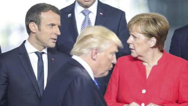 El presidente estadounidense, Donald Trump, pasa por delante de la canciller alemana, Angela Merkel, y del presidente francés, Emmanuel Macron, durante la foto de familia de los asistentes a la cumbre de la OTAN.