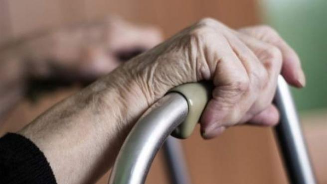 Las manos de una anciana se agarran a un andador.