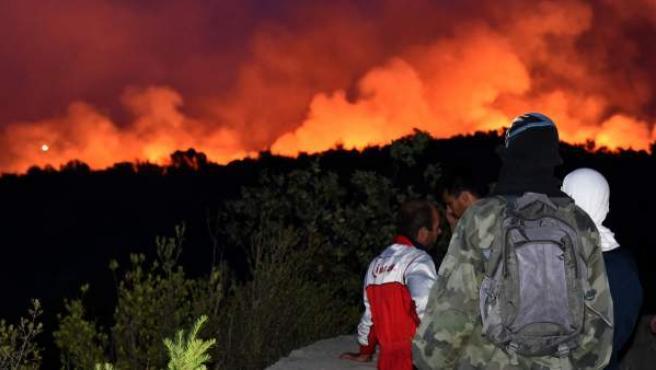 Turistas observan un incendio forestal desde una iglesia junto a un monasterio en la península de Lustica (Montenegro). Al menos cien turistas han sido forzados a evacuar la península, ubicada en el sureste del país.
