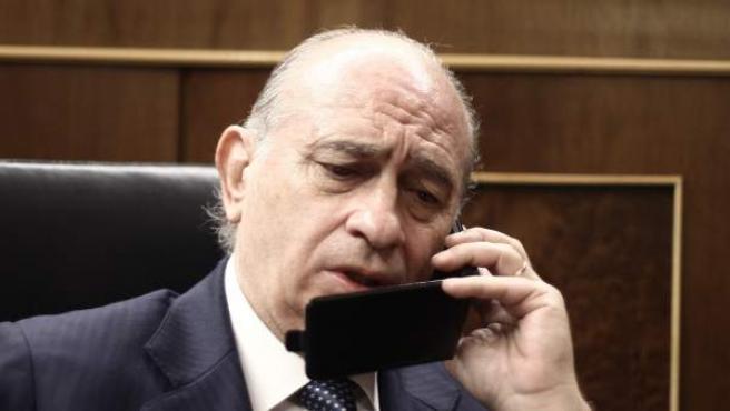 Jorge Fernández Díaz, hablando por teléfono en el hemiciclo.